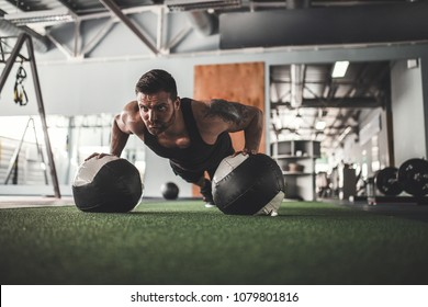 Plank it. Confident bearded, tattoed muscled man wearing sport wear and doing plank position on gym balls while exercising in gym.