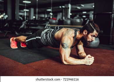 Plank it. Confident muscled young man wearing sport wear and doing plank position while exercising in gym.