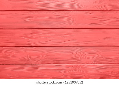 Plank texture of wood table painted in Living Coral color of the Year 2019. Trendy pastel coloured background.