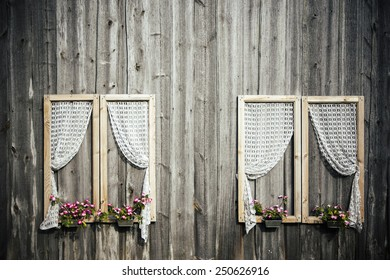 Plank wall with decorative windows, curtains and flower pots.