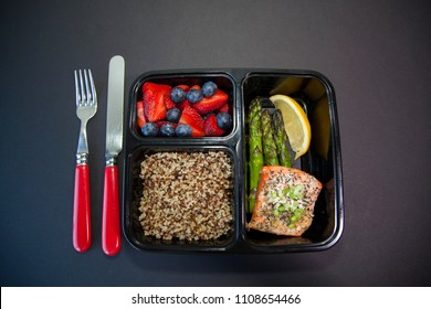 Planned meal container with salmon, asparagus, quinoa and fruit for a healthy lunch.