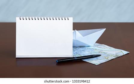 Planned trip: map, notebook, pen, boat