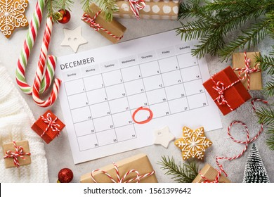 Planner page with Christmas gift boxes and decoration around. 25th of December marked with red circle on calendar. Xmas preparation concept.