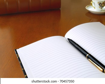 Planner with pen,binder and cup on the table