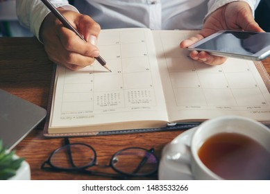 Planner plan Schedule Calendar and reminder agenda, work online at home. Women hand planning daily appointment and note holiday trip in diary at office desk. Calendar reminder event concept