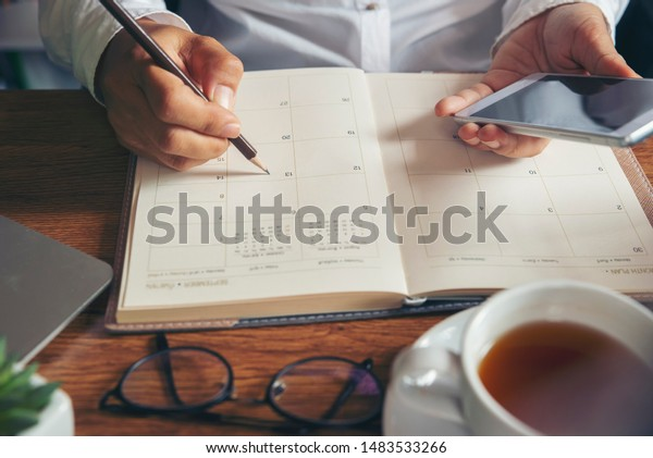 Planner plan Schedule Calendar and reminder agenda, work online at home. Women hand planning daily appointment and note holiday trip in diary at office desk. Calendar reminder event concept.