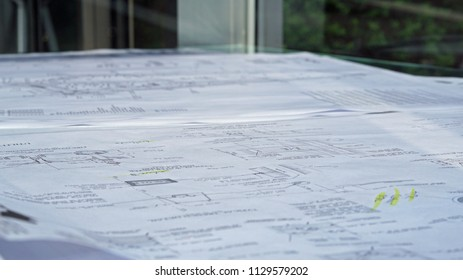Planning blueprints on conference room table.