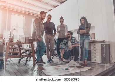 Planning business together. Handsome young man with beard pointing at large paper laying on floor while his colleagues looking at it and smiling