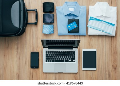 Planning a business trip: bag, formal clothing, credit cards and plane tickets on a desk with laptop, smartphone and tablet, traveling and technology concept