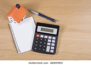 Planning and costing home improvements concept with a calculator, pen and notebook with a small model of a house on a wooden desk