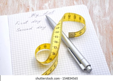 Planning of a diet. A notebook with inscription - My Diet, a measuring tape and pen