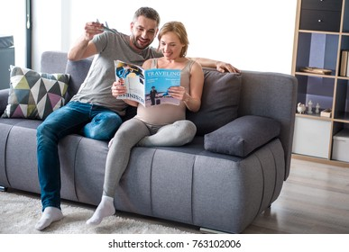 Planning future journey. Full length portrait of cheerful loving couple reading magazine about traveling while sitting on sofa at home. Man is holding plane toy while his pregnant wife is smiling