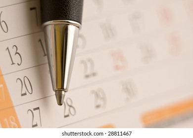 Planning future tasks on a calendar using a ballpoint pen.