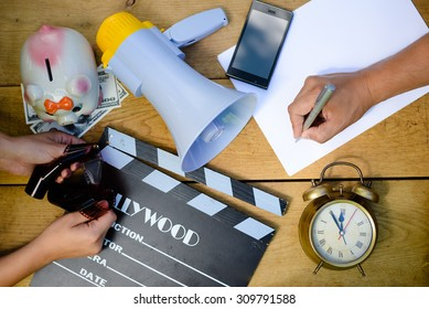 Planning to make movie with clapperboard, megaphone and piggy bank, mobile phone and alarm clock. Organize and coordinate teamwork to write scenario.