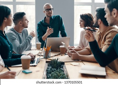 Planning new business strategy. Group of young modern people in smart casual wear discussing something while working in the creative office