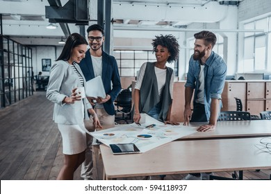 Planning new business strategy. Group of young business people in smart casual wear working together and smiling while standing near the wooden desk in office
