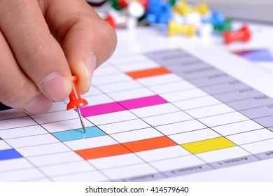 Planning paper with Calendar pin closeup at businessman hand