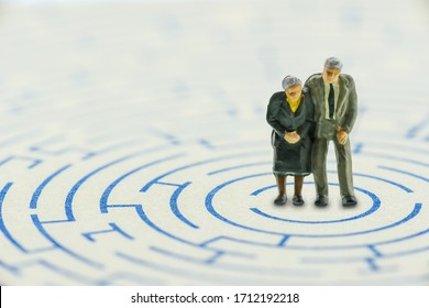 Planning for retirement / avoid top concerns or issues for retiree, financial concept : Senior couple in a complex maze try to find the way to handle or escape from problems of unexpected longer life