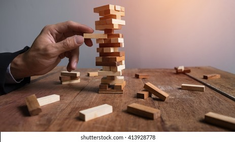 Planning, risk and strategy in business, businessman and engineer gambling placing wooden block on a tower.