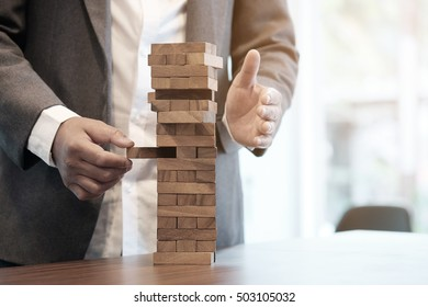 Planning, risk and strategy in business, businessman gambling placing wooden block on a tower with vintage tone and Risk management and insurance concept, leadership has solution for problem.