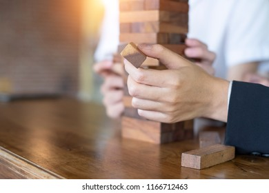 Planning, risk and strategy in business, business woman gambling placing wooden block on a tower