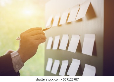 Planning, risk and strategy of project management in business, businessman putting his ideas on white board during a presentation in conference room. Focus in hands with pen writing in flipchart