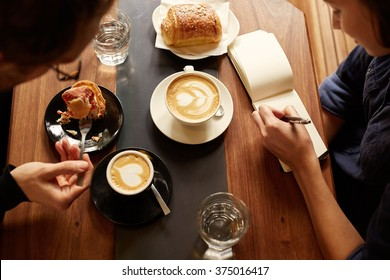 Planning session at a cafe between two people with coffee