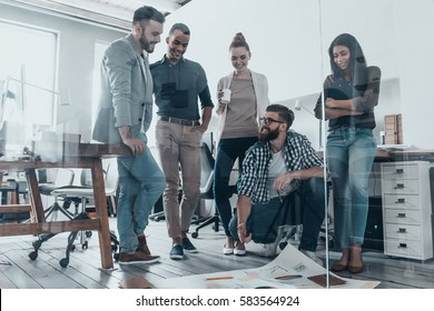 Planning strategy together. Handsome young man with beard pointing at large paper laying on floor while his colleagues looking at it and smiling