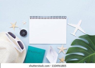 Planning summer holidays, tourism and vacation background. Travelers notebook with accessories on blue pastel table top view. Flat lay.