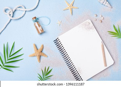 Planning summer holidays, tourism and vacation background. Travelers notebook with accessories on blue pastel table top view. Flat lay style.