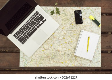 Planning travel on wood table outside with map, laptop, knife, notebook and pen