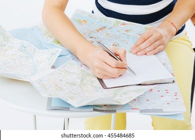 Planning a trip using maps and taking notes for the itinerary
