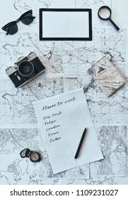 Planning vacation. High angle shot of sunglasses, photo camera, compass, magnifying glass, paper with written checklist and passport lying on map