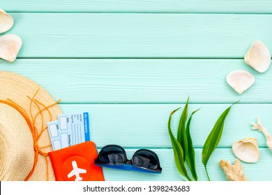 Planning vacation to the seaside with straw hat, sun glasses, passport, tickets mint green background top view mock-up