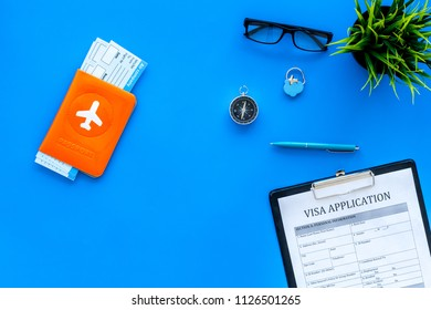 Planning vacation. Visa prosessing. Airplane tickets near passport cover with airplane silhouette, visa application form, compas on blue background top view copy space