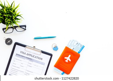Planning vacation. Visa prosessing. Airplane tickets near passport cover with airplane silhouette, visa application form, compas on white background top view copy space