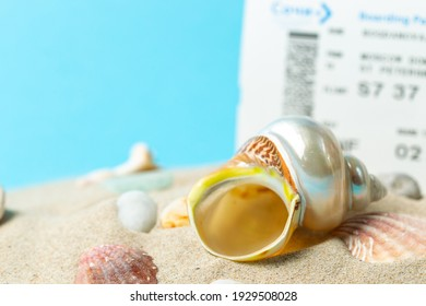 Planning a vacation, a weekend at the sea. Sea sand with shells on a blue background close-up and plane tickets. Selective focus, copy space