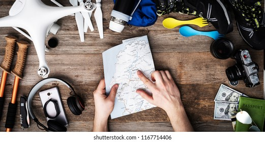 Planning where to travel with useful equipent on the wooden background