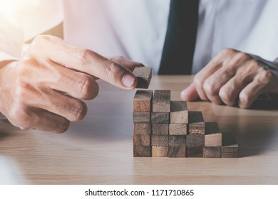 Planning,risk ans strategy in business.Hand of man has piling up and stacking a wooden block.