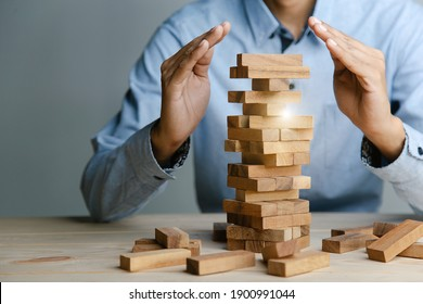 Planning,risk and strategy in business, businessman placing wooden block on a tower.