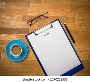 Plans for 2019 on board with coffee and glasses on wooden background