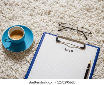 Plans for 2019 on board with coffee and glasses, flat lay