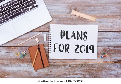 Plans for 2019 text written on paper note pad, grunge wood table flat lay shot from above