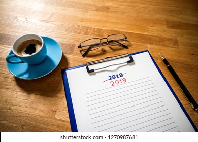 Plans 2019 versus 2018 on wooden board with coffee and glasses, flat lay