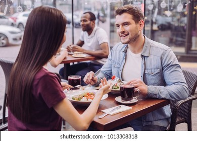 Plans for evening. Attractive energetic couple communicating and posing at cafe while handsome man smiling