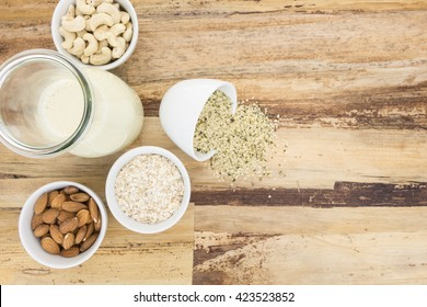Plant based milk and and bowls with ingredients, on wooden background