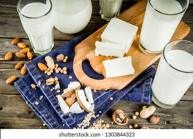 plant based vegan food and drink, Non-dairy milk and cheese tofu - from almond, nuts, soy beans, oats and coconut, wooden background copy space
