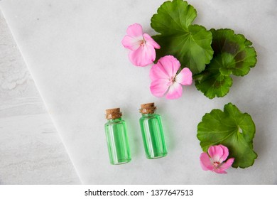 Plant extract in viles with geranium leaves and pink flowers, top view