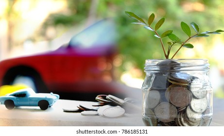 plant growing out of coins in jar with blurred car background.Saving money, Investment And Interest .Car loans or finance concept.