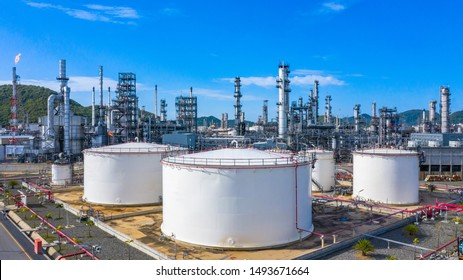 Oil refinery and petrochemical plant industrial working with fire and blue sky background, Aerial view oil and gas refinery at day.